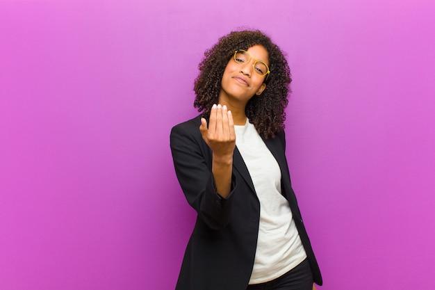 Jonge zwarte zakenvrouw voelt zich gelukkig, succesvol en zelfverzekerd, staat voor een uitdaging en zegt: kom maar op! of je verwelkomen