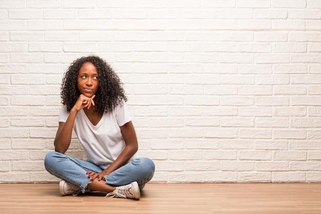 Jonge zwartezitting op houten vloer die en omhoog denken denken, verward over een idee