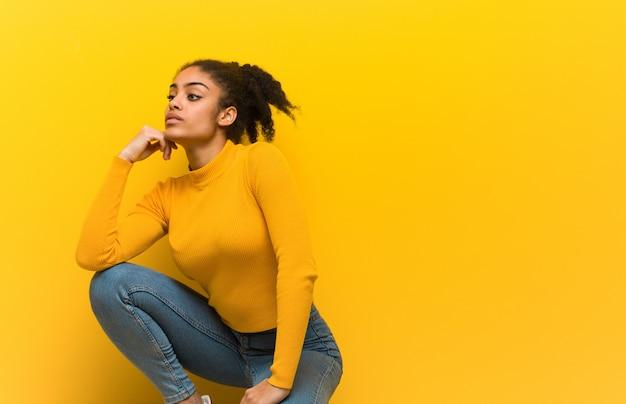 Jonge zwartezitting over een oranje muur