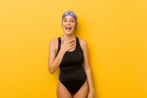 Jonge zwemmer blanke vrouw lacht hardop hand op de borst te houden.