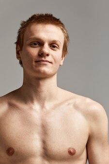 Jonge zwemmer in uitstekende fysieke vorm, op een grijze achtergrond met kopieerruimte, oproep voor sport, reclamebanner.