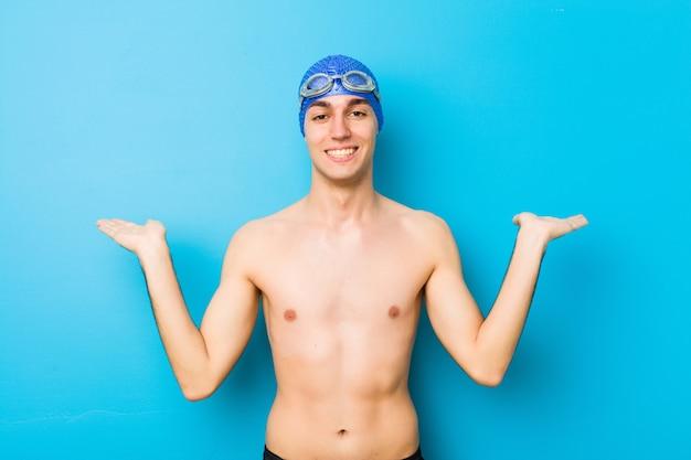 Jonge zwemmer man maakt schaal met armen, voelt zich gelukkig en zelfverzekerd.
