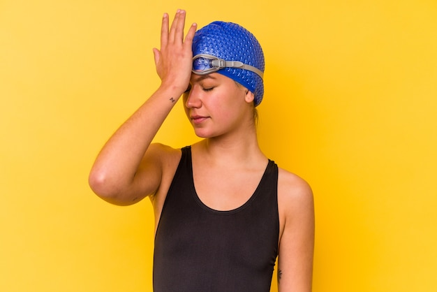 Jonge zwemmer venezolaanse vrouw geïsoleerd op gele achtergrond iets vergeten, voorhoofd met palm slaan en ogen sluiten.