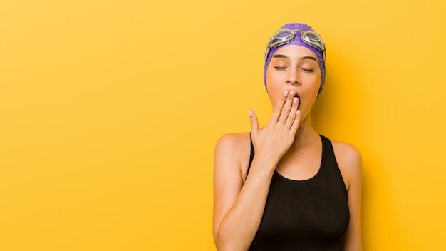 Jonge zwemmers kaukasische vrouw die tonend een vermoeid gebaar die mond behandelen met hand geeuwen.
