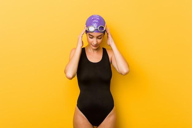 Jonge zwemmers kaukasische vrouw wat betreft tempels en het hebben van hoofdpijn.