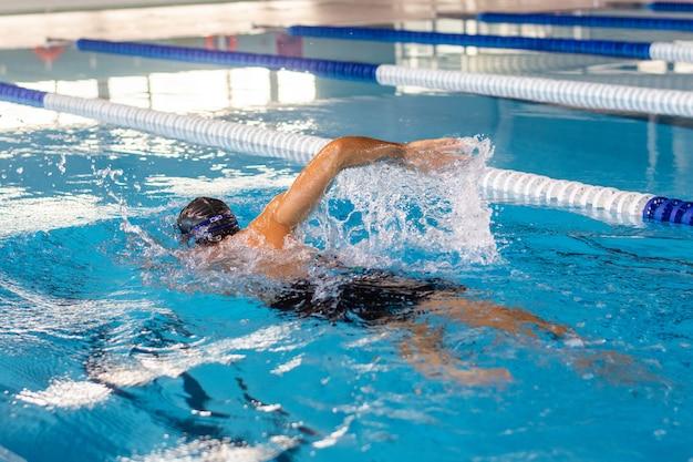 Jonge zwemmersmens die in olympische pool zwemmen