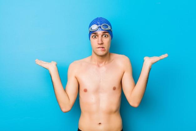 Jonge zwemmersmens verward en twijfelachtig schouders ophalen om een exemplaarruimte te houden.