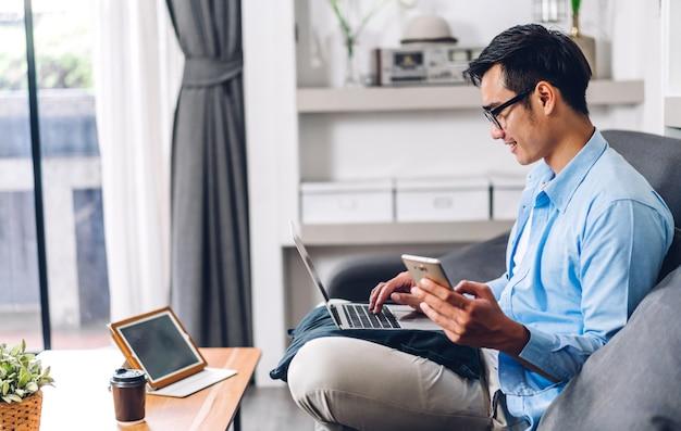 Jongelui die de aziatische mens ontspannen thuis gebruikend laptop computer het werken en videoconferentievergadering.