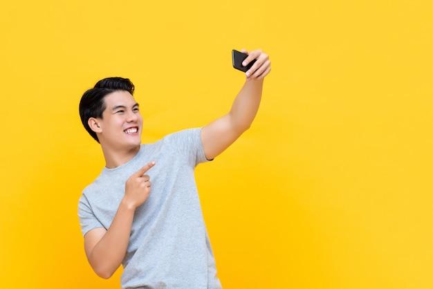 Jongelui die de knappe aziatische mens glimlachen die selfie met smartphone nemen