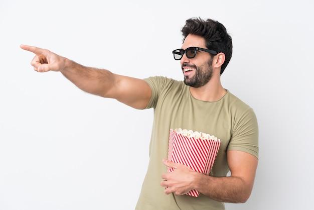 Jongelui die een grote kom popcorns over geïsoleerde muur houden