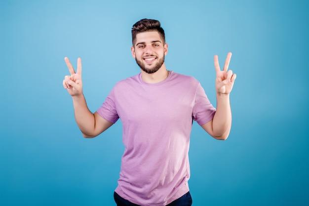 Jongelui die gebaarde mens glimlachen die vredesgebaar met vingers tonen