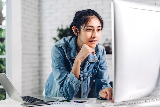 Jongelui die gelukkige aziatische vrouw ontspannen die thuis het gebruiken van bureaucomputer het werken en videoconferentievergadering online chat gebruiken. creatief meisje die op toetsenbord typen. werk van huisconcept