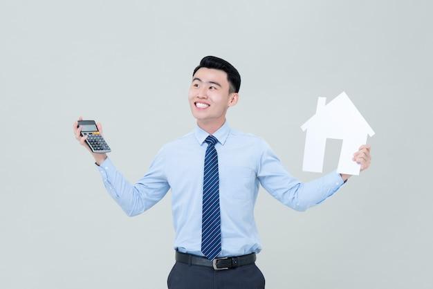 Jongelui die het aziatische mannelijke calculator van de makelaar in onroerend goedholding en huisknipsel glimlachen