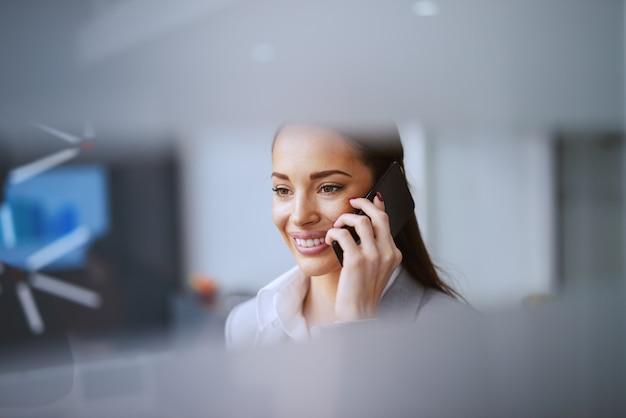 Jongelui die kaukasische mooie onderneemster glimlachen die telefoongesprek hebben terwijl status in bureau. je bouwt geen bedrijf op. je bouwt mensen op en vervolgens bouwen mensen het bedrijf op.
