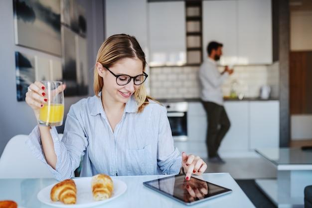 Jongelui die kaukasische vrouw glimlachen die met oogglazen bij eettafel zitten, glas vers sap houden en tablet gebruiken.
