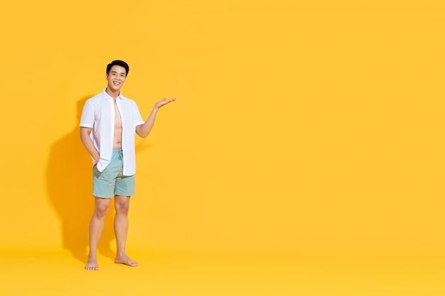 Jongelui die knappe aziatische mens in strandkledij glimlachen die open palmgebaar doen die lege copyspace in de zomergeel geïsoleerde muur tonen