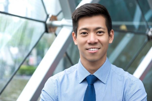 Jongelui die knappe aziatische zakenman in bureaulounge glimlachen