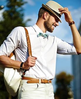 Jongelui die modieuze sexy knappe modelmensentoerist glimlachen in toevallige doeklevensstijl in de straat in hoed met zak