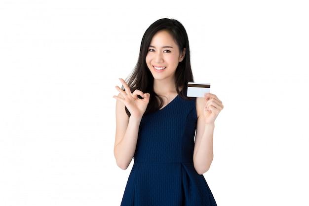 Jongelui die mooie aziatische vrouw glimlachen die creditcard met okeygebaar tonen