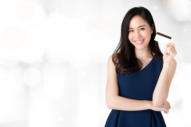 Jongelui die mooie aziatische vrouw glimlachen die creditcard ter beschikking aanbieden
