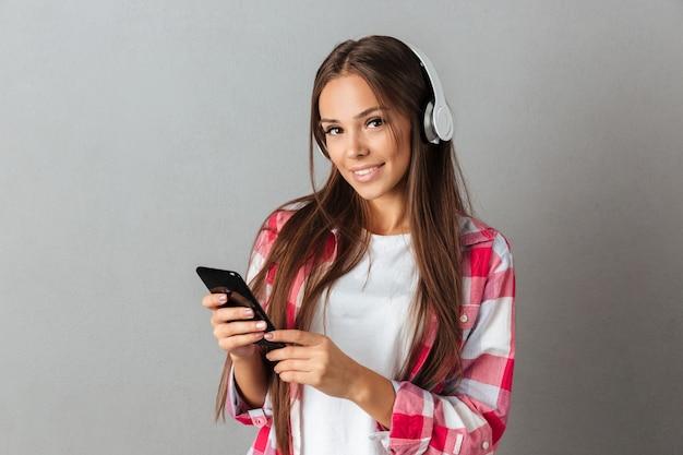 Jongelui die mooie donkerbruine vrouw met lang haar glimlachen, het luisteren muziek met witte hoofdtelefoons