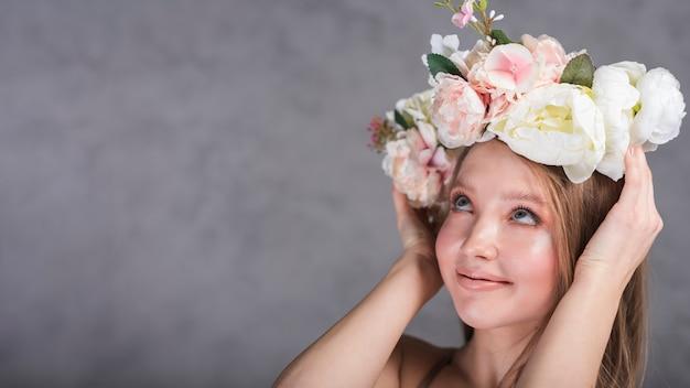 Jongelui die romantische dame glimlachen die mooie bloemkroon houden