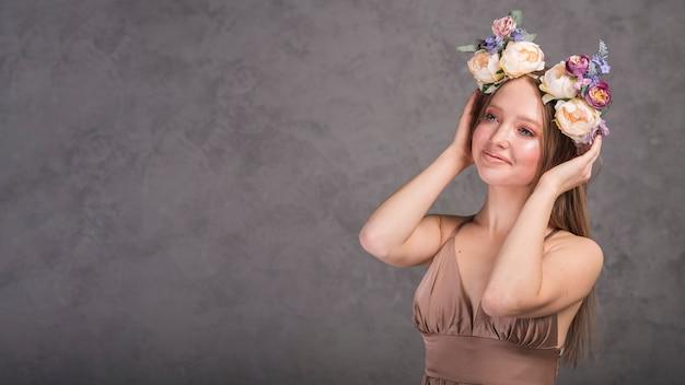 Jongelui die romantische dame in kleding met mooie bloemkroon glimlachen