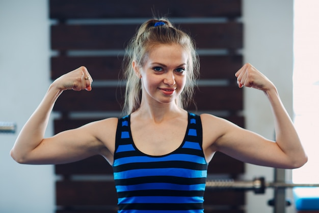 Jongelui die sportieve vrouw glimlachen die bicepsen tonen