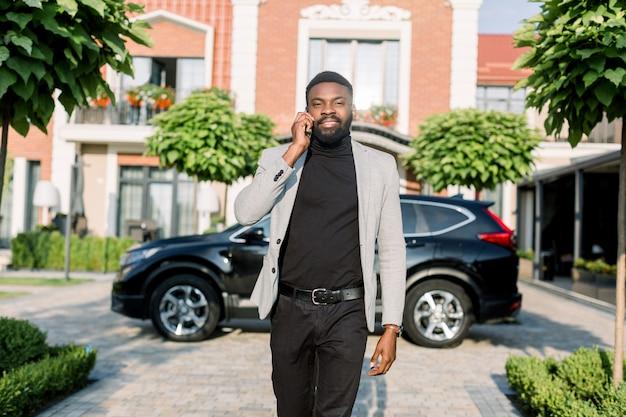 Jongelui die zwarte bedrijfsmens in een kostuum glimlachen die door smartphone spreken die in openlucht dichtbij een zwarte auto en moderne baksteengebouwen lopen