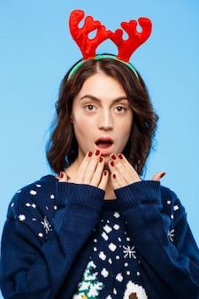 Jongelui geamuseerd mooi donkerbruin meisje in gebreide sweater en kerstmisrendiergeweitakken die over blauwe muur glimlachen