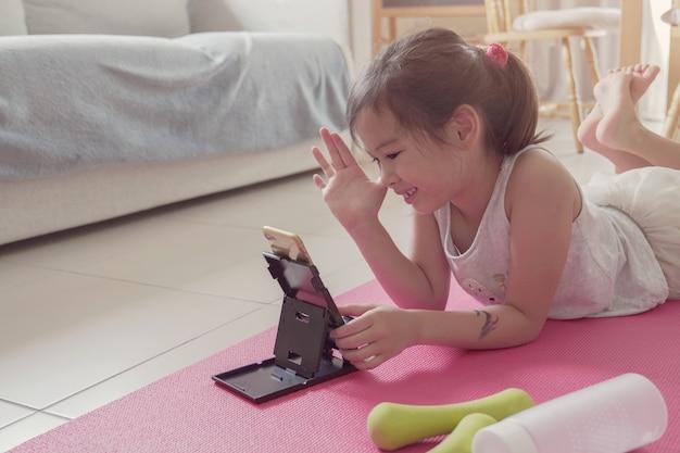 Jongelui gemengd aziatisch meisje die stromende video's op laptop, training thuis training, klasse van gezoem de online oefeningen, sociaal afstandsconcept bekijken