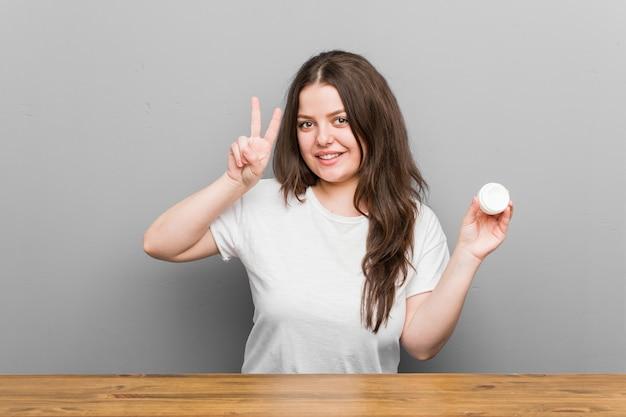 Jongelui plus grootte curvy vrouw die een vochtinbrengende crème houden die overwinningsteken tonen en breed glimlachen.