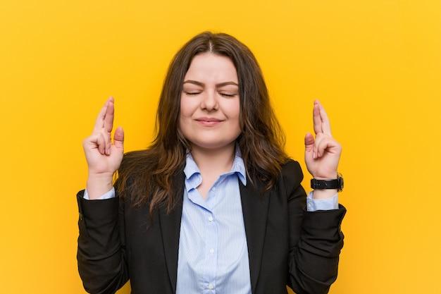 Jongelui plus grootte kaukasische bedrijfsvrouw die vingers kruisen voor het hebben van geluk