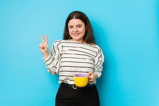Jongelui plus groottevrouw die een theemok houden die nummer twee met vingers tonen.
