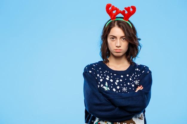 Jongelui verstoord mooi donkerbruin meisje in gebreide sweater en kerstmisrendiergeweitakken over blauwe muur