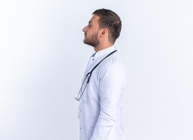 Jongeman arts in witte jas en met stethoscoop om nek ziet er zelfverzekerd uit en staat zijwaarts over witte muur