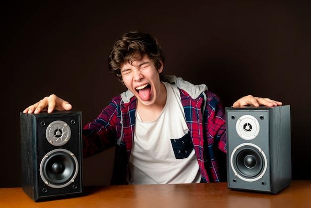 Jongeman audiofiel luister naar luide muziek uit luidsprekers f