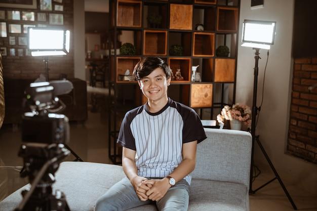 Jongeman blogger maken beoordeling met behulp van de camera op de voorgrond