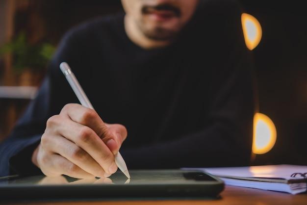 Jongeman die computerlaptop of tablet gebruikt voor werk en online communicatie leert vanuit huis, cyberspace-onderwijstechnologie voor zakenmensen of studenten die werken, hipster zakenman