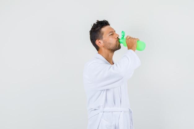 Jongeman drinkwater na bad in witte badjas, vooraanzicht.