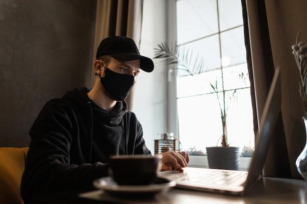 Jongeman freelance professional met zwart medisch masker en pet in trendy hoodie die op laptop werkt en koffie drinkt in café. pandemie en beschermingsconcept