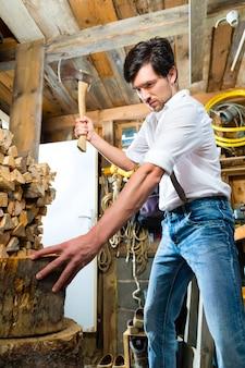 Jongeman hakken brandhout in bergchalet