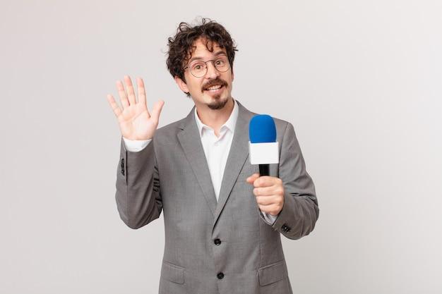 Jongeman journalist die vrolijk lacht, met de hand zwaait, je verwelkomt en begroet