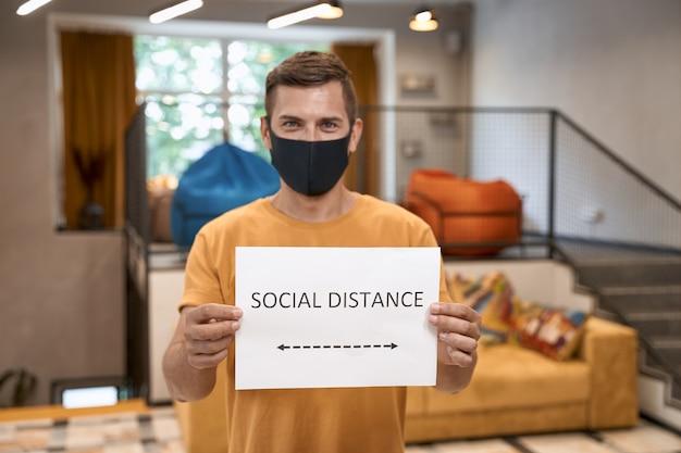 Jongeman kantoormedewerker met zwart beschermend masker met papier met tekst sociale afstand op