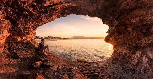 Jongeman silhouet in een kustgrot naast het strand van hendaia, in baskenland.
