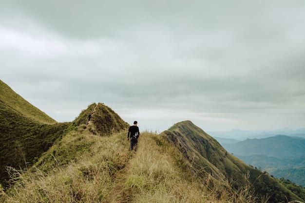 Jongeman wandelen hij liep langs de bergkam om de hoogten te veroveren. bij khao chang puak, kanchanaburi in thailand.