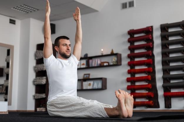 Jongeman yoga traint in de fitnessruimte. concept van meditatie en gezondheid.