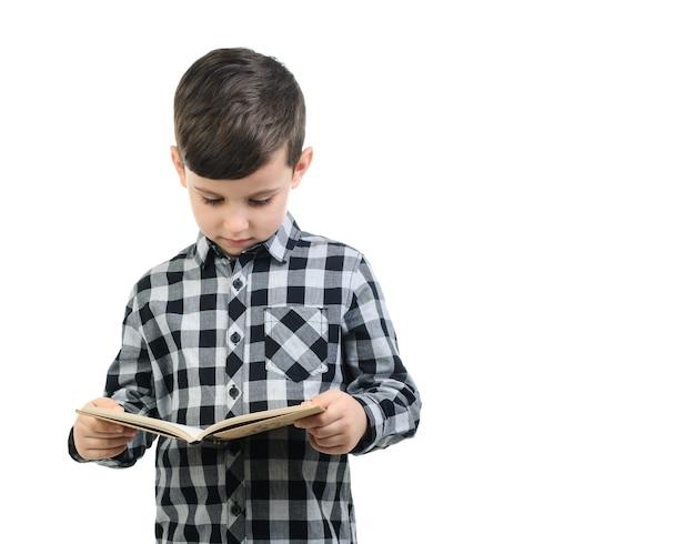 Jongen 6 jaar oud in grijs shirt leest op witte geïsoleerde achtergrond, jongen op zoek naar een boek, jongen lezen; onderwijs
