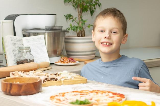 Jongen 7-10 in t-shirt die pizza in keuken kookt, kind glimlacht en wijst met vinger naar pizza
