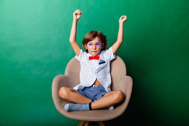Jongen 7 jaar oud zit op een stoel en hief zijn handen boven zijn hoofd, geïsoleerd op een groene achtergrond. portret van een knappe jongen